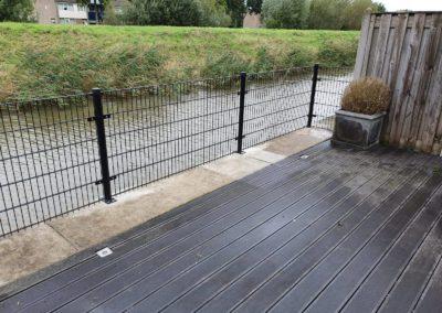 DSM hekwerk op voetplaten op terras aan rand van een water.