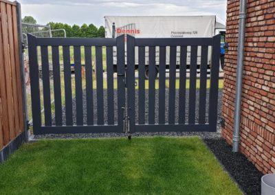 Dubbele brede spijlen poort tussen muur en hout beton schutting. (2)