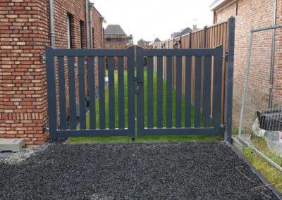 Dubbele brede spijlen poort tussen muur en hout beton schutting.
