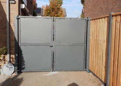 Dubbele draaipoort met dichte platen grijs naast hout beton schutting achteraanzicht
