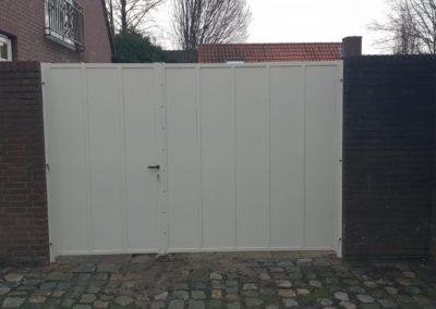 Dubbele draaipoort met dichte platen verticaal geheel zichtdicht wit ongelijke verdeling tussen muren vooraanzicht