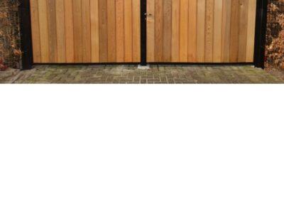 Dubbele draaipoort met houtvulling met strips tegen inkijk tussen dubbel staafmat begroeid met haag dichtbij