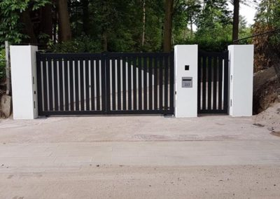 Dubbele spijlenpoort met brede spijl tussen kolommen met enkele poort