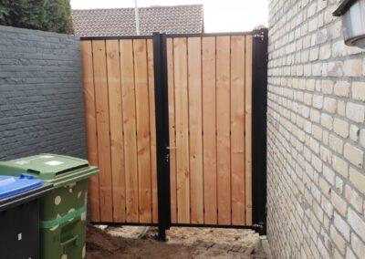 Enkele draaipoort houtvulling beide zijdes bekleed met vast hekdeel tussen 2 muren achteraanzicht