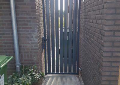 Enkele draaipoort met brede spijl tussen muren zonder staanders