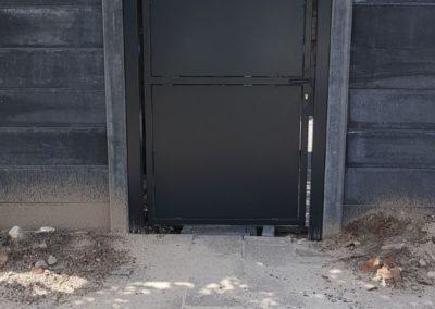 Enkele draaipoort met dichte platen tussen betonnen schutting